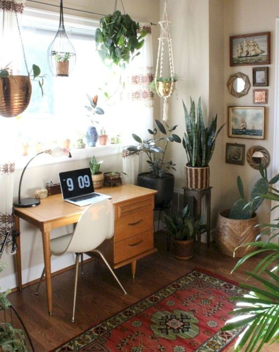 a mid-century modern working space with a small stained desk, a white chair, a printed rug, potted plants, a gallery wall and a table lamp