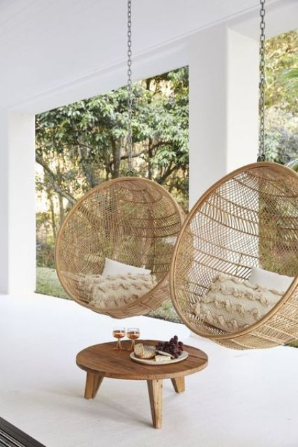 a minimalist back porch with sphere pendant chairs with pillows, a low table is a lovely and chic space for any outdoors