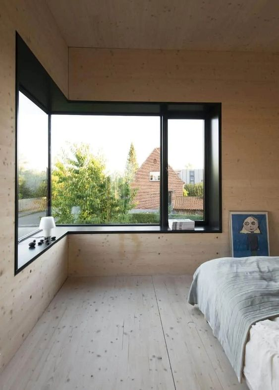 a minimalist bedroom clad with light stained wood, a large corner window and a black windowsill that features a cool view