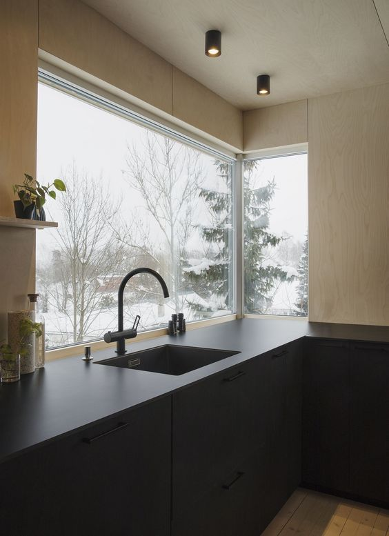 a minimalist kitchen done with light stained plywood and with sleek dark cabinets and black fixtures plus a corner window to enjoy the views