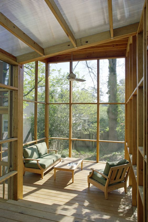 a minimalist screened porch with simple wooden furniture and green upholstery is a lovely outdoor sitting zone to enjoy