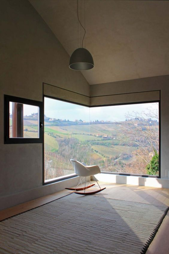 a minimalist space with a corner window that offers amazing views of outside and a single chair to meditate to this beauty here