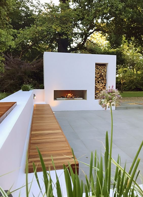 a minimalist terrace with a white fireplace with fireood storage, a cool bench of sutcco and wood is amazing to relax here