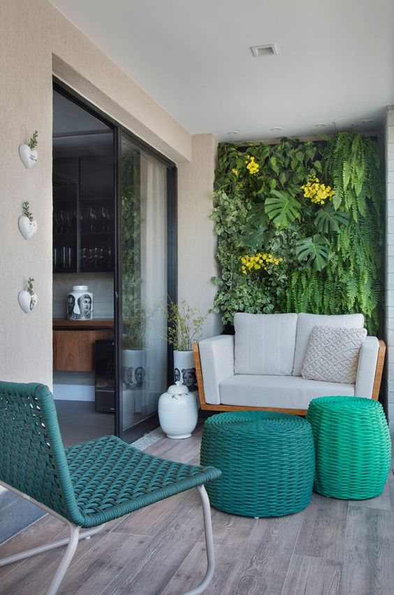 a modern and bright balcony with a living wall, a cozy loveseat, bright wicker side tables and a teal woven chair plus some blooms