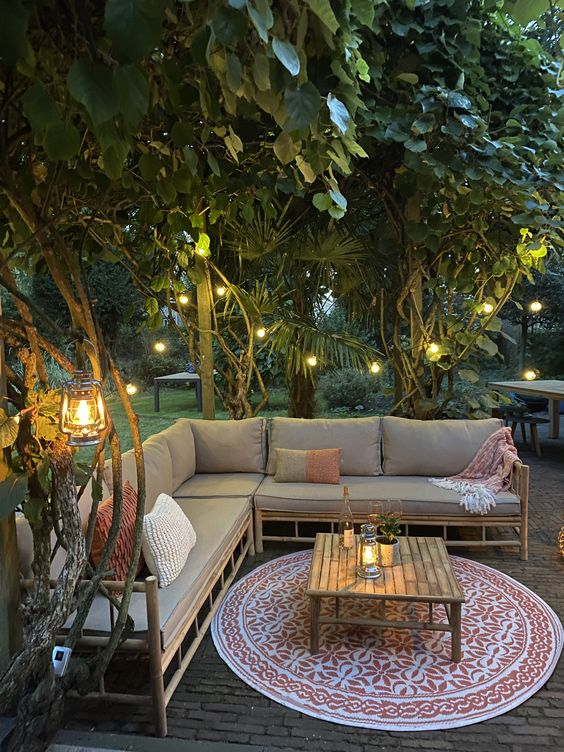 a modern and cozy patio with a large bamboo corner sofa with neutral textiles, a printed rug and textiles, a wooden table and string lights