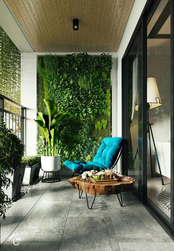 a modern and inviting balcony with a living wall, potted greenery, a wood slice coffee table and a teal lounger is a lovely space to be