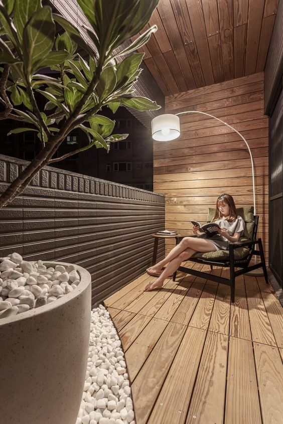 a modern and stylish balcony clad with stained wood, with a large dark stained chair, a side table and a potted plant plus pebbles on the floor