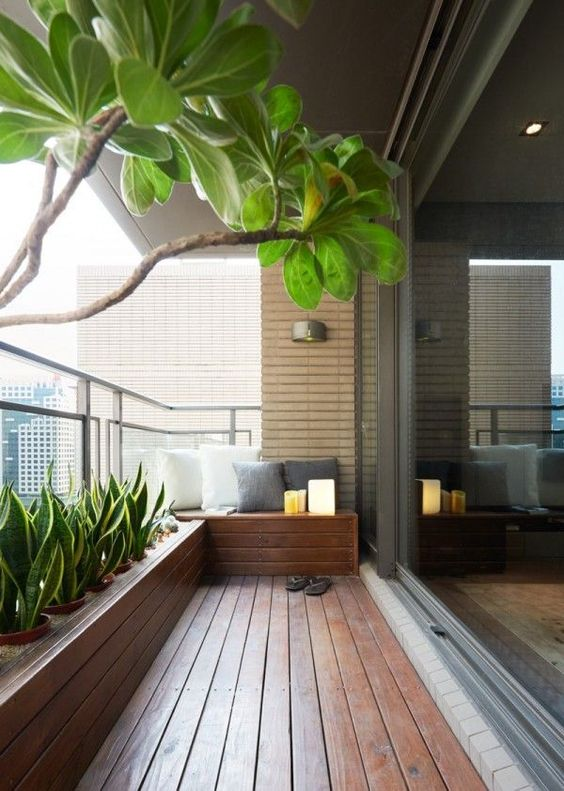 a modern and welcoming balcony with a rich-stained deck, a built-in bench and a flower bed with lots of succulents