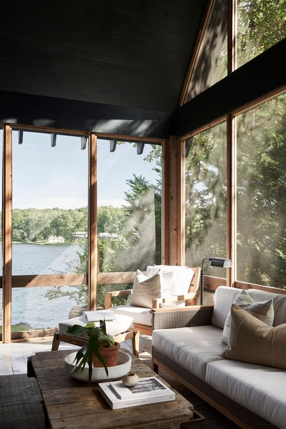 a modern and welcoming screened porch with neutral rattan furniture, printed pillows, a low wooden coffee table, lovely lake views