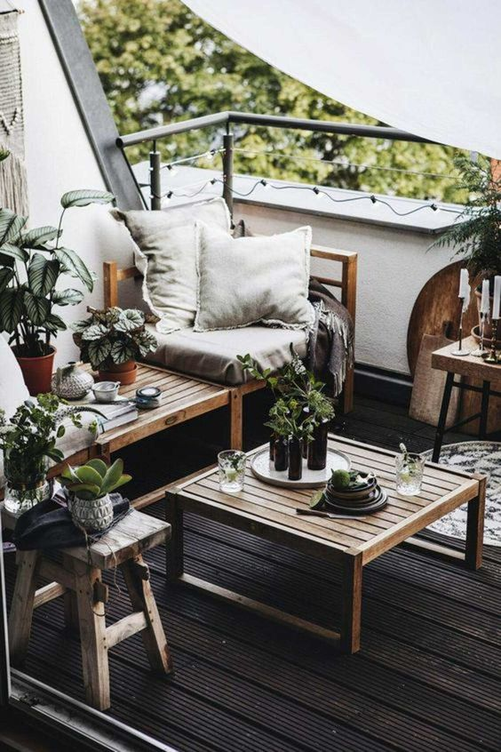 a modern balcony with wooden planked furniture, potted greenery, candles in candleholders, tableware and teaware