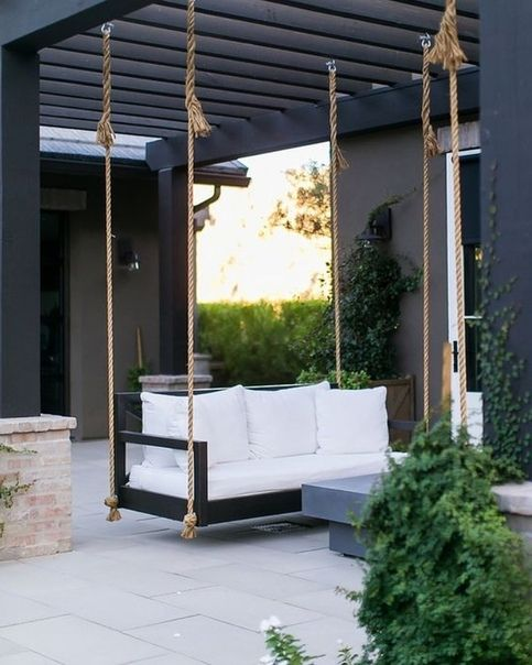 a modern black pergola with a black hanging daybed, white bedding and a stone coffee table in front of it is a cool space