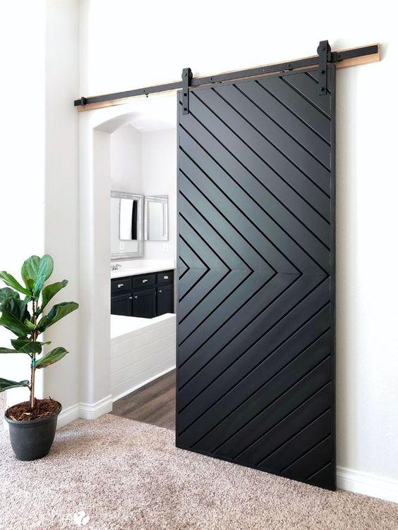 a modern black sliding door with a chevron pattern is a gorgeous idea for a modern farmhouse home