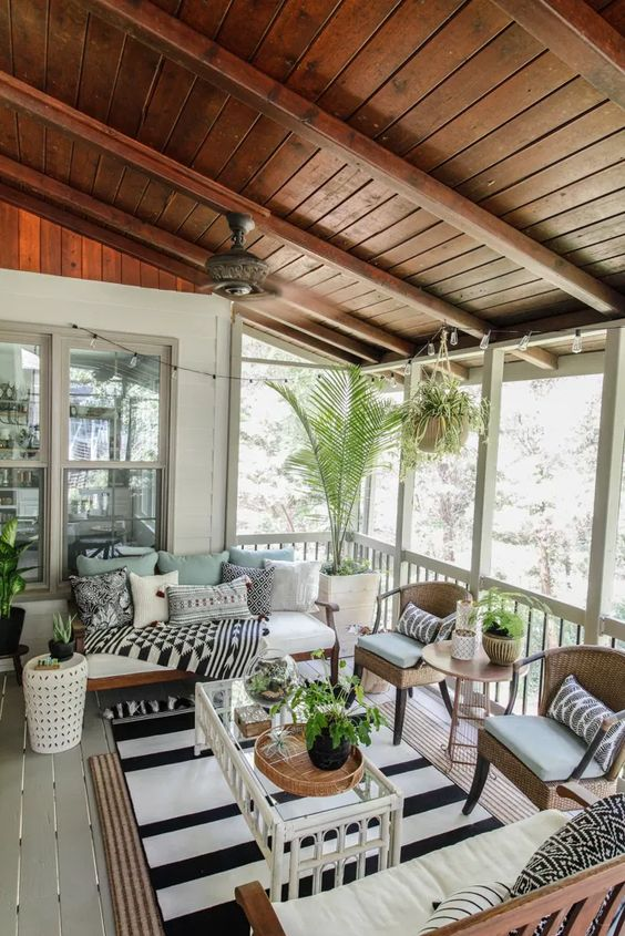 a modern boho screened porch with simple stained wood and rattan furniture, a glass coffee table, potted plants and printed textiles