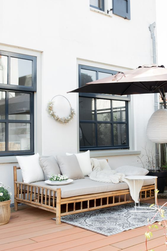 a modern deck with a large umbrella, a bamboo daybed wih neutral bedding, a side table and some potted blooms