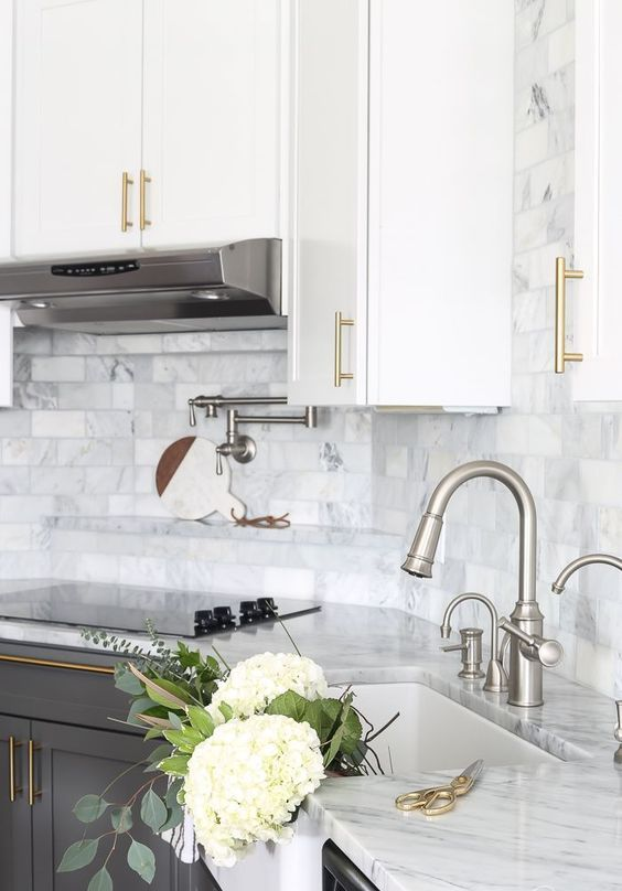 a modern farmhouse kitchen with two tone cabinets and with gold handles plus chromatic faucets and applainces looks great and chic