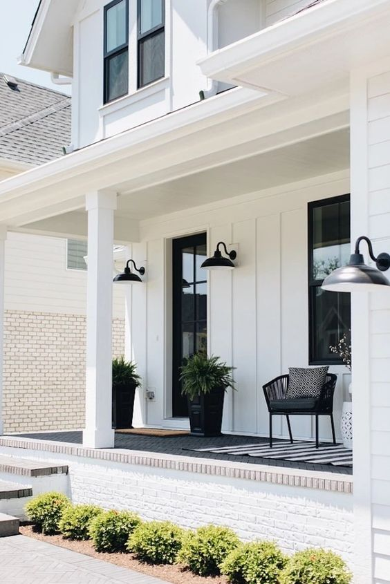 a modern farmhouse porch with layered rugs, a black chair and black planters, greenery, printed textiles and sconces