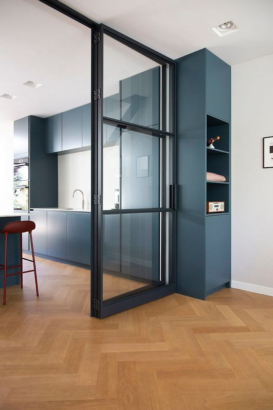 a modern framed glass sliding door that separates the kitchen from the rest of the space and doesn't prevent the spaces from being filled with light