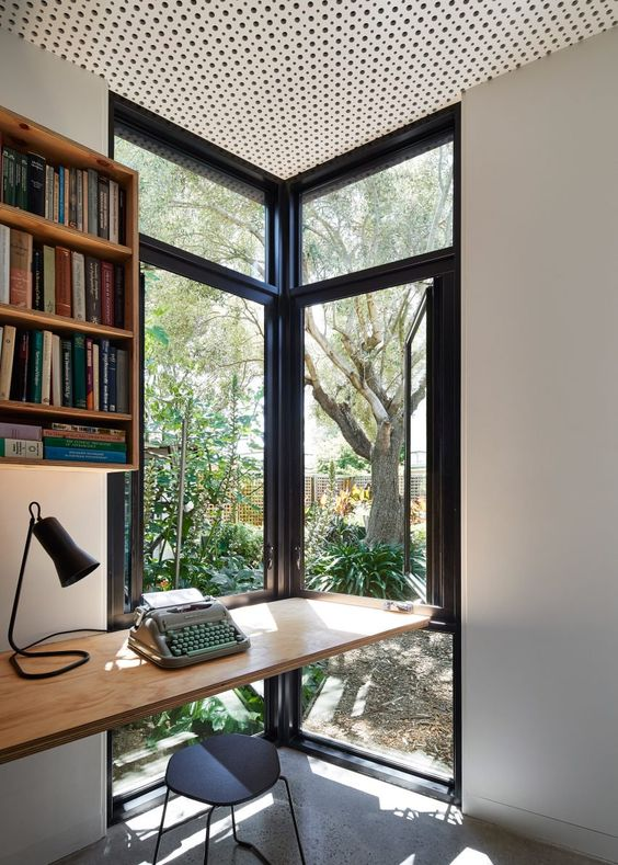 a modern home office with a corner window, a floating desk and bookshelf, a black stool and a lovely view of the garden