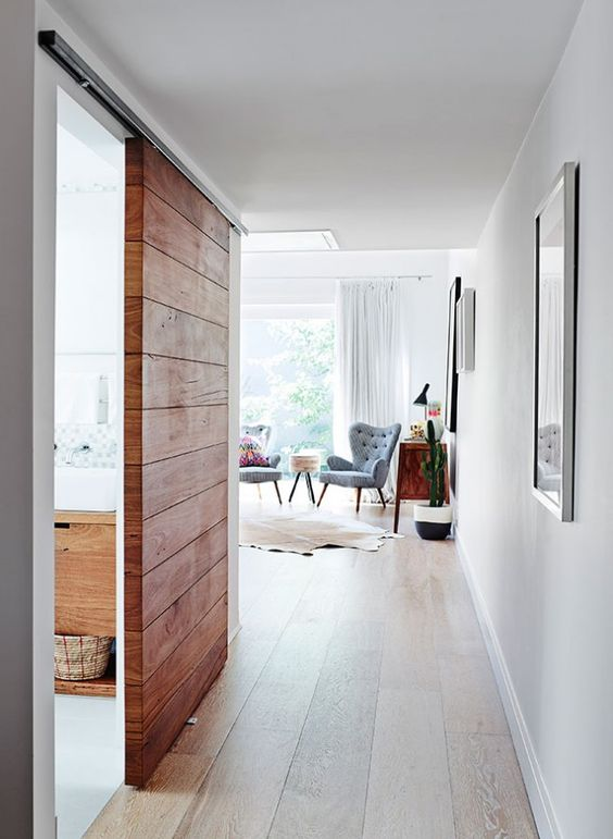 a modern rich-stained wood sliding door without any handles is a stylish idea for a modern or farmhouse space
