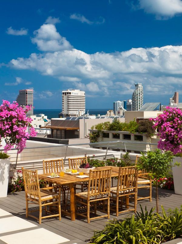 a modern rooftop terrace with a wooden deck, a bamboo dining set with potted greenery and blooms and a gorgeous view