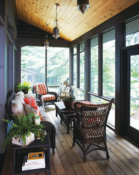a modern rustic screened porch done with dark walls and frames, dark woven furniture, bright upholstery and pillows, potted plants and lamps