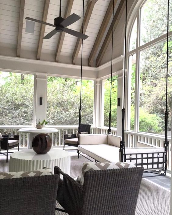 a modern screened porch with a hanging bench, black wicker chairs, side and coffee tables, some plants and cool views