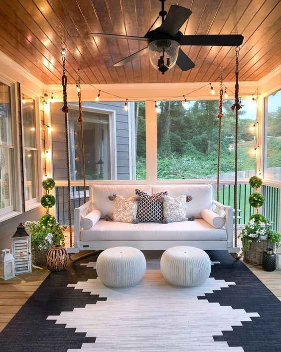 a modern screened porch with a white hanging sofa, potted plants and blooms, candle lanterns and white poufs plus a graphic rug