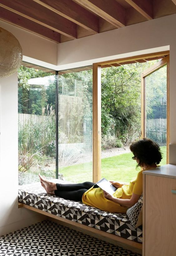 a modern space with a large corner window that allows going outside, with a daybed and printed bedding for relaxing here