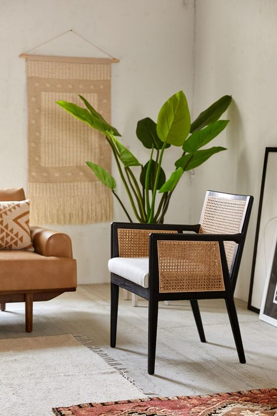 a modern teak chair with cane arms and a back is a very cool and chic idea for a modern or boho space, it's a bold solution with a retro feel