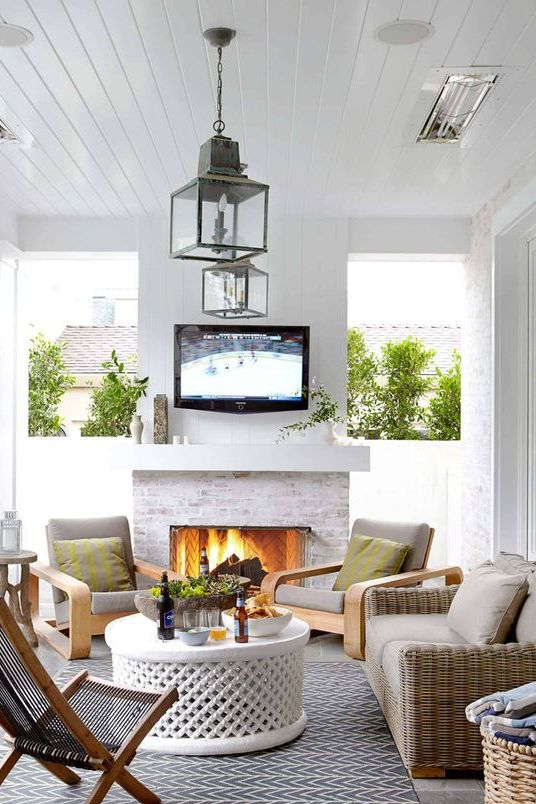 a modern terrace with a white fireplace, wood and wicker furniture, neutral textiles, candle lanterns and a white round table