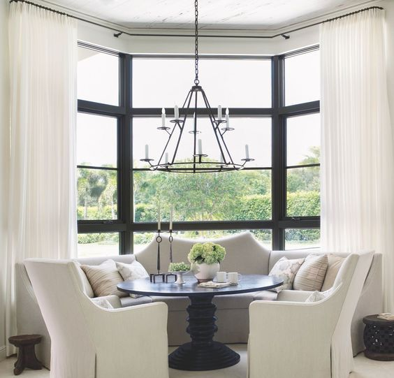 a monochromatic nook at the bow window with black framing, with neutral curtains and a built in sofa, a black round table