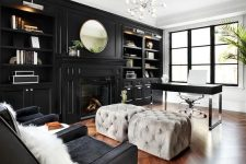 a moody home office with a glazed wall, a black storage unit with built-in shelves and a fireplace, a black desk and grey poufs, black chairs and a lovely chandelier