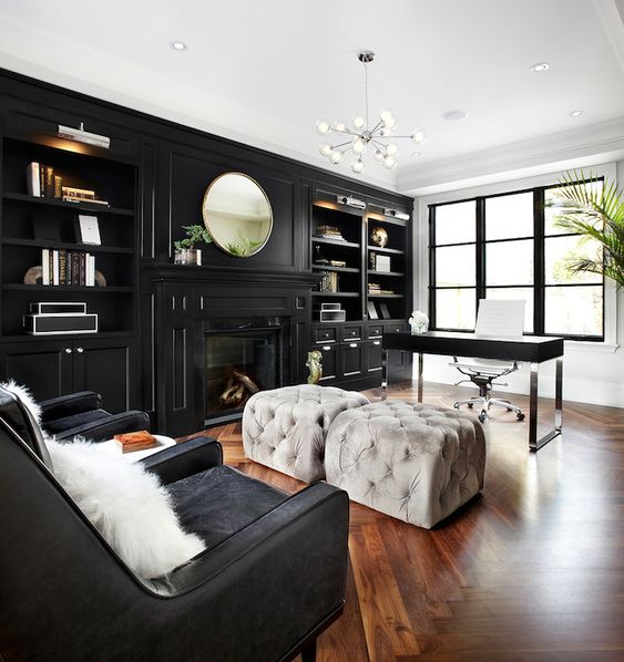 a moody home office with a glazed wall, a black storage unit with built in shelves and a fireplace, a black desk and grey poufs, black chairs and a lovely chandelier