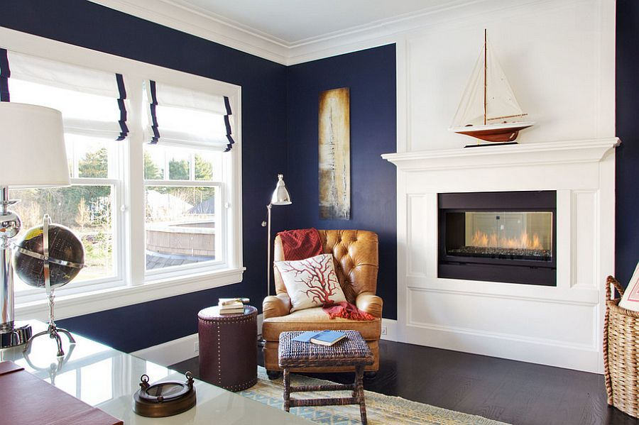 a nautical home office with navy walls, a fireplace, a glass desk, a leather chair, printed textiles and some vintage lamps and decor