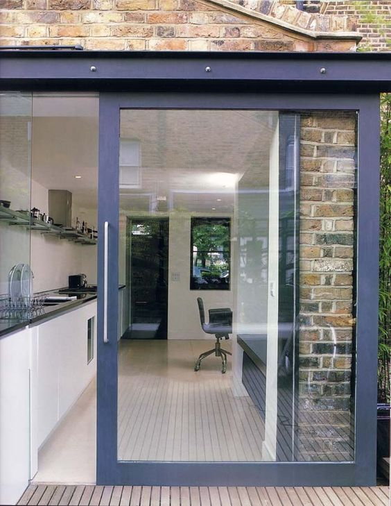 a navy glass sliding door allows to open the kitchen to the terrace any time and lets much natural light in and provides cool views