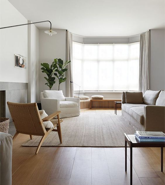 a neutral and airy living room done in greys, with a bow window, some daybeds, neutral furniture, a floor lamp and potted plants
