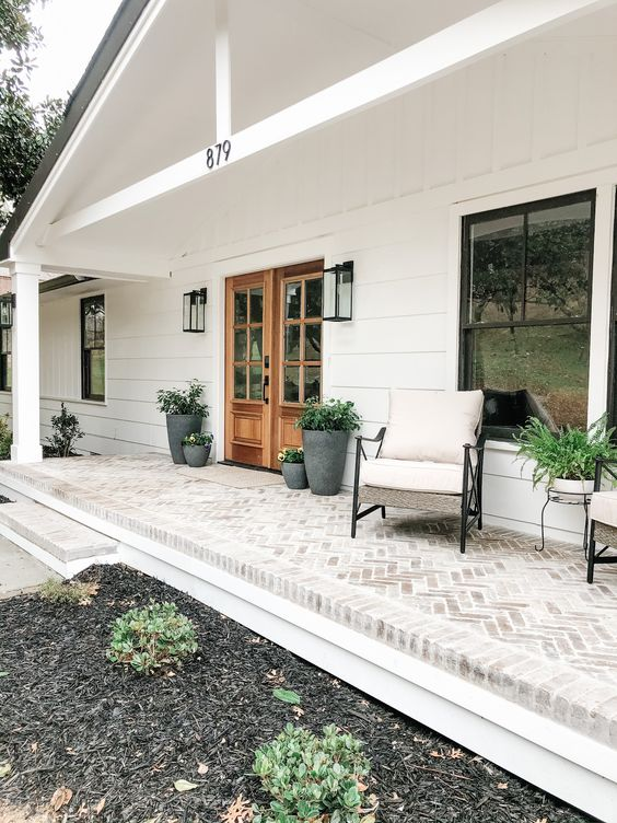 a neutral and simple farmhouse porch clad with bricks, with neutral furniture, potted greenery and plants is a welcoming and cool space