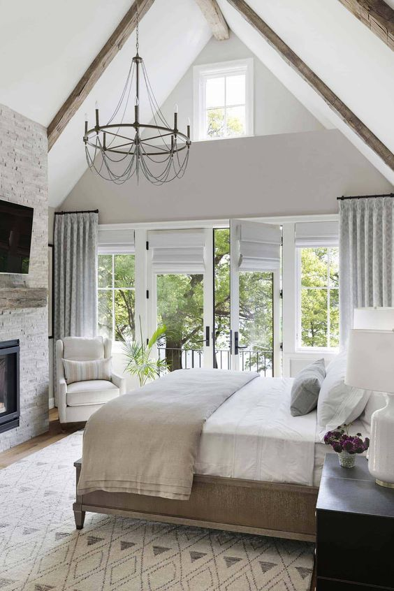 a neutral farmhouse bedroom with a stone clad fireplace, a wooden bed with neutral bedding, neutral and printed textiles, a vintage chandelier