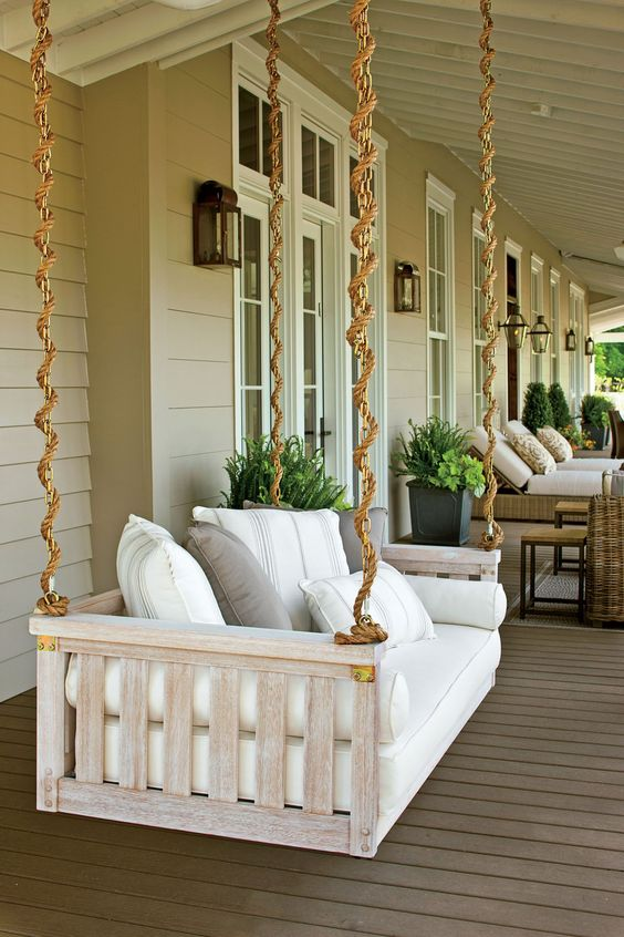 a neutral hanging daybed with printed pillows and bedding is a perfect idea for a farmhouse porch and looks cool