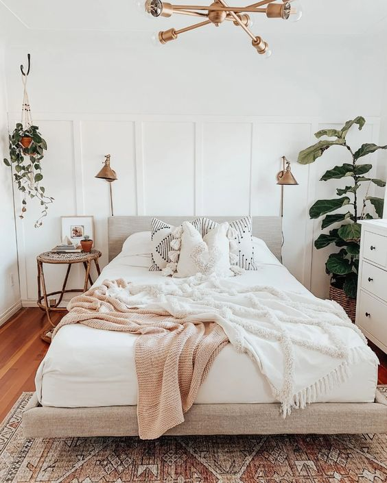 a neutral mid-century modern bedroom with a white paneled wall, a neutral upholstered bed, neutral bedding, rattan nightstands and brass lamps