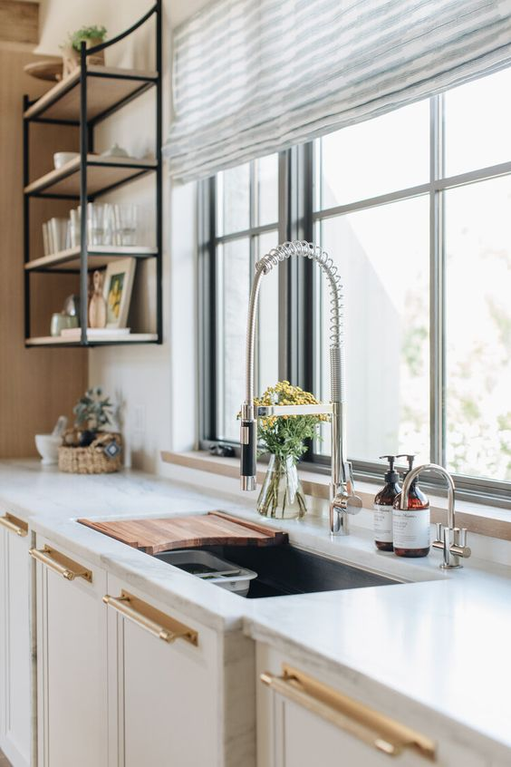 a neutral modern kitchen with gold handles and a chromatic faucet is a very chic idea and the kitchen looks statement and chic