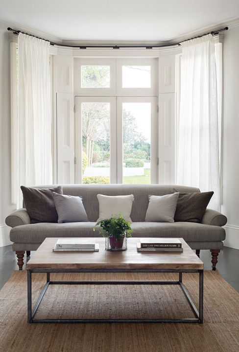 a neutral modern living room with a bow window styled with shutters and neutral curtains, a grey sofa, a jute rug and a wooden table