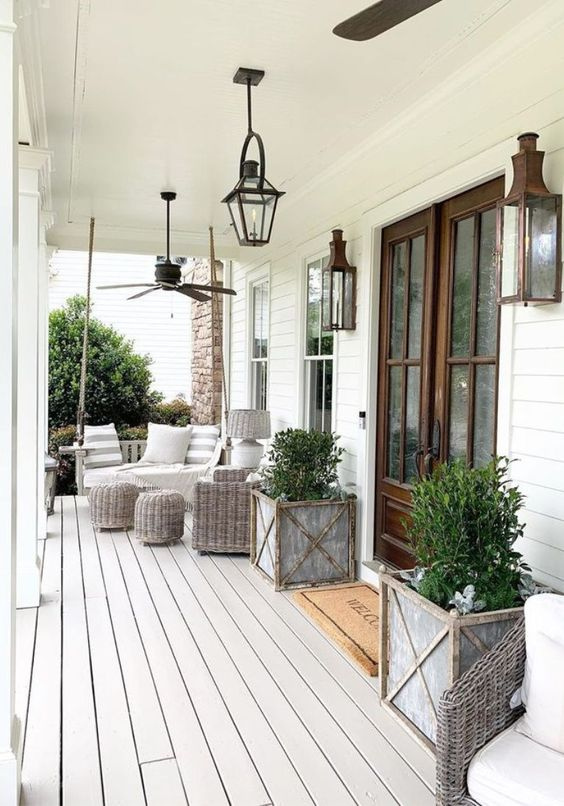 a neutral rustic porch with grey wicker furniture, potted greenery, candle lanterns and printed textiles is a cool space