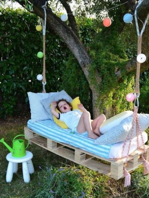 a pallet hanging daybed with bright bedding, with strign lights that are weaving the bed and a stool for a cozy space