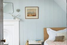 a pastel bedroom with light blue planked walls, a built-in fireplace, stained furniture, animal skin rugs, some art and a mirror