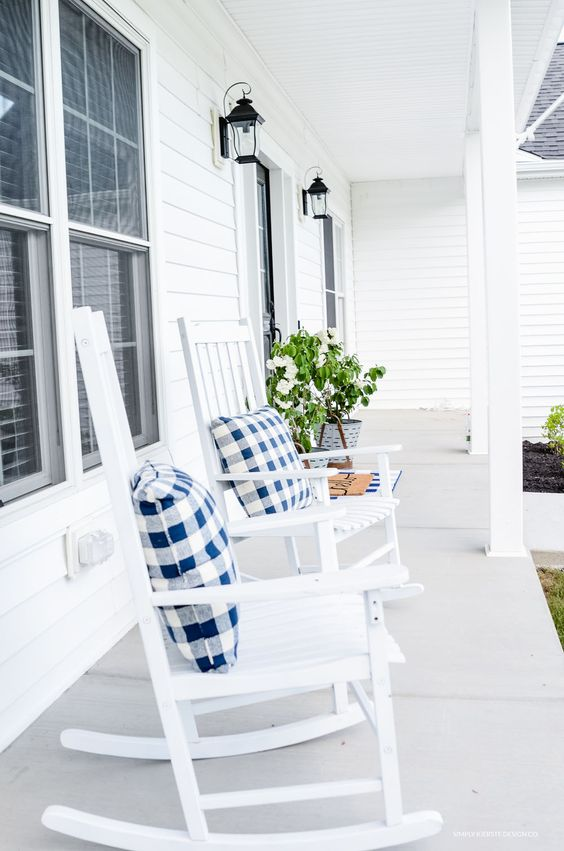 a pretty and airy summer farmhouse porch done in white, with white rockers, potted greenery and lanterns on the wall