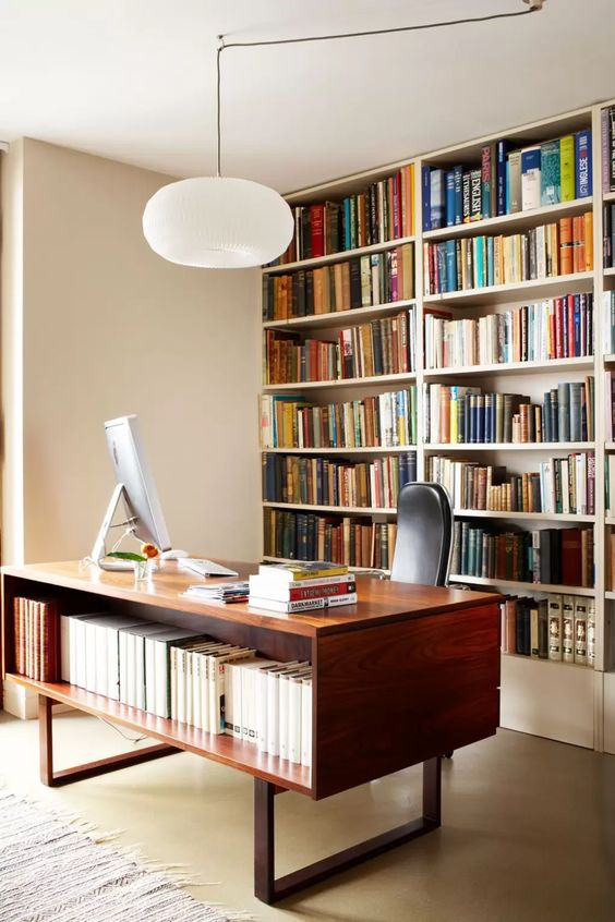 a pretty and cool mid-century modern home office with a large bookcase that takes a whole wall, a stained desk with books, a leather chair and a pendant lamp