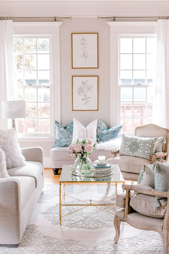a pretty and welcoming neutral living room with tall French windows, refined vintage furniture, a glass coffee table and printed pillows