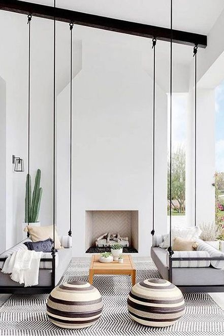 a pretty contemporary terrace with a white fireplace, hanging sofas, printed textiles, potted greenery and cacti is a bold idea