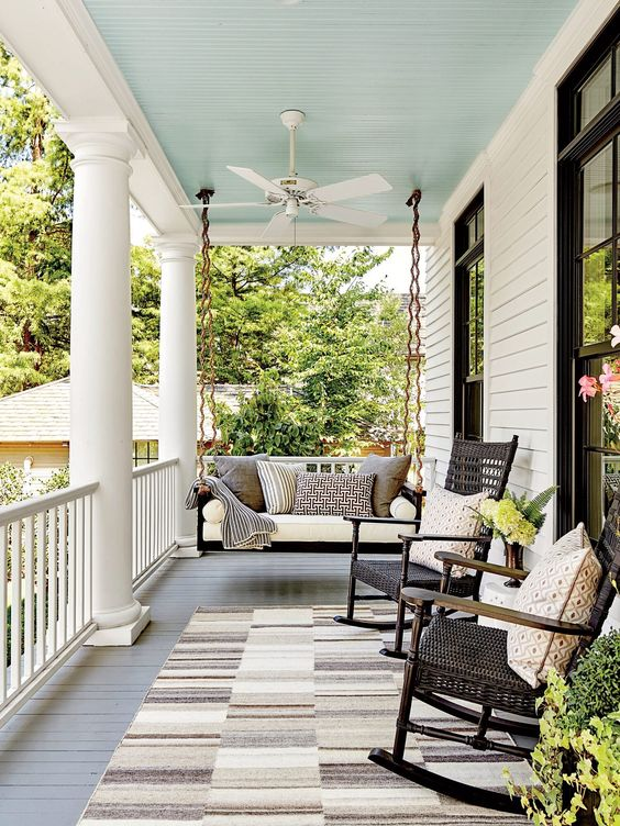 a pretty farmhouse porch with a striped rug, black rockers and a black hanging bench, printed pillows and greenery and blooms